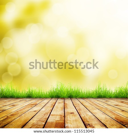 Fresh autumn green grass with green bokeh and sunlight and wood floor. Beauty natural background