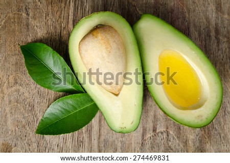fresh avocado and  half of avocado like a bowl for oil on wooden background - stock photo