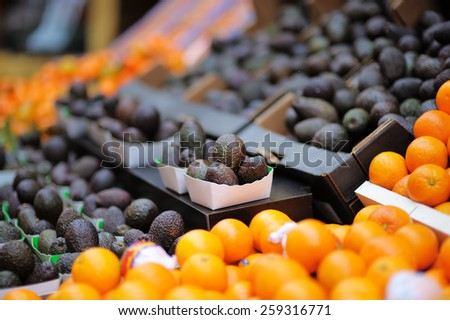 Fresh avocado and oranges at farmers market - stock photo