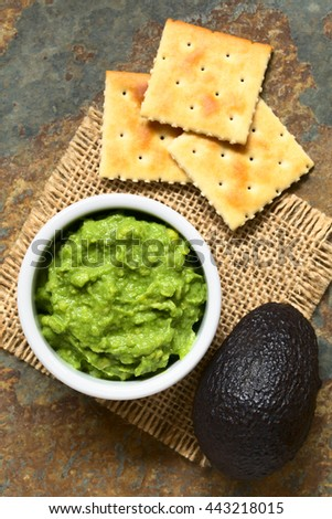 Fresh avocado cream or guacamole with soda crackers on the side, photographed overhead with natural light (Selective Focus, Focus on the top of the avocado cream)