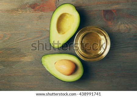 Fresh avocado oil on wooden table, top view - stock photo