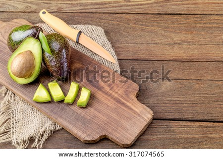 Fresh avocado on cutting board over wooden background - stock photo
