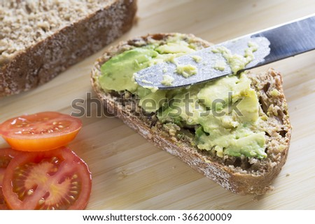 Fresh avocado on thick sliced whole wheat bread with tomatoes.