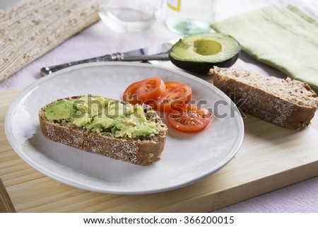 Fresh avocado on thick sliced whole wheat bread with tomatoes. - stock photo