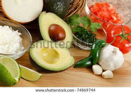 Fresh avocado surrounded by onion, tomato, garlic, jalepeno peppers and lime, ready for preparing guacamole - stock photo