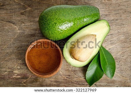 fresh avocado with avocado oil in the wooden bowl isolated on wooden background.top view - stock photo