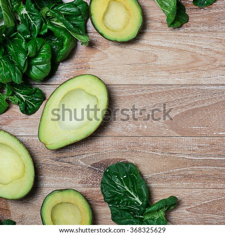 Fresh avocados and green leaves of salad on the wooden table - stock photo