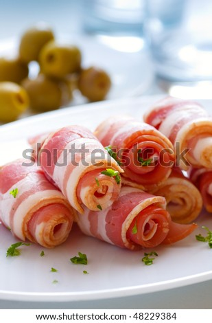 Fresh bacon rolls with herbs on the white plate,closeup - stock photo