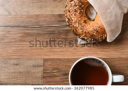 Fresh bagel and hot cup of coffee on a rustic wood table with copy space. - stock photo