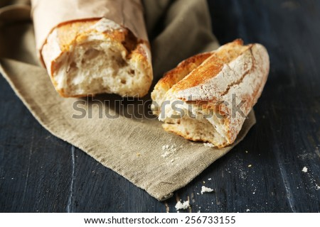 Fresh  baguette on wooden table, close up - stock photo
