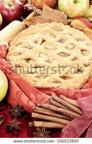 Fresh baked apple pie  surrounded by fall leaves and fresh ingredients. - stock photo