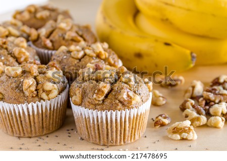 Fresh baked banana walnut and chia seed muffins with ingredients sitting on wooden table - stock photo