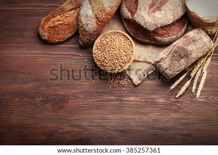 Fresh baked bread and a bowl of wheat grains on the wooden background - stock photo