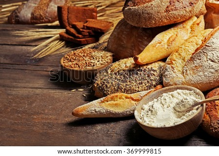 Fresh baked bread, flour and wheat on the wooden table