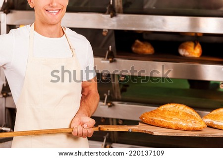 Fresh baked bread for you. Cropped image of confident young man in apron taking fresh baked bread from oven and smiling  - stock photo