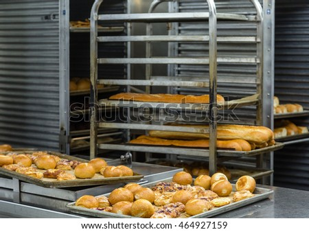 Fresh baked bread on racks and pans in a commercial kitchen