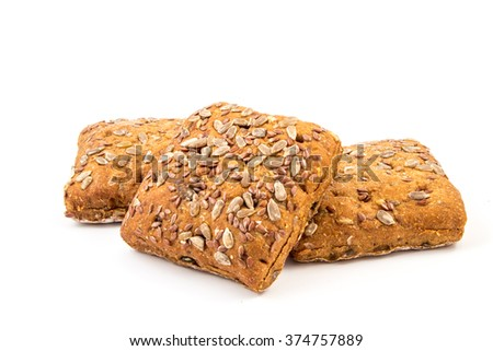Fresh baked bread or bun with sesame and sunflower seeds topping on white background - stock photo