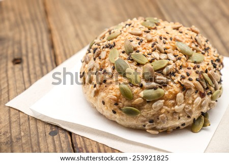 Fresh baked bread or bun with sesame and sunflower seeds topping on wood background - stock photo