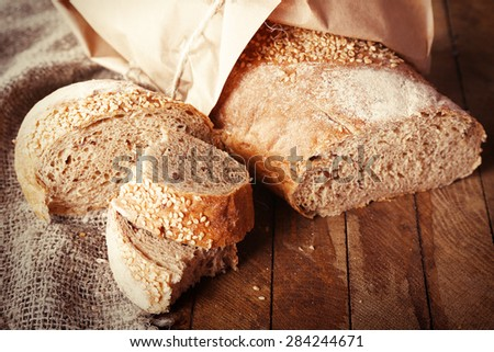 Fresh baked bread wrapped in paper, on wooden background - stock photo