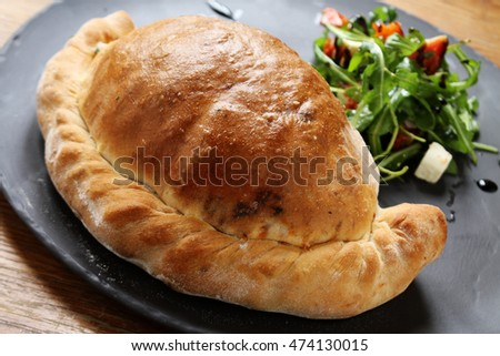 fresh baked calzone pizza in dish