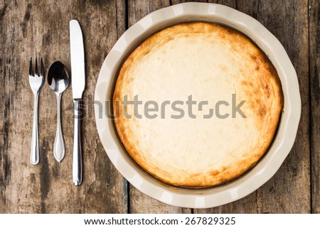 Fresh baked cheesecake on wooden table with silverware. Top view image of pie on wood background - stock photo