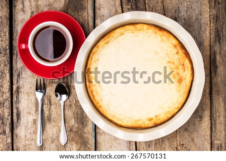 Fresh baked cheesecake with cup of black tea on wooden table. Top view image of breakfast eating background - stock photo