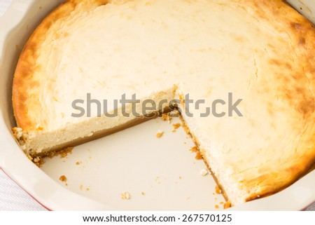 Fresh baked cheesecake with cut of piece. Recipe dessert background - stock photo