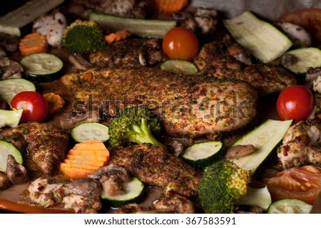 Fresh baked chicken breast with vegetables (cherry tomatoes, zucchini and carrot) and mushrooms closeup