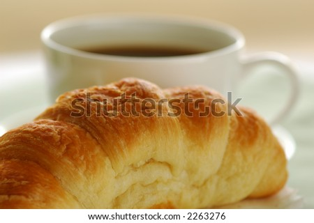 Fresh-baked croissant and cup of coffee. Shallow DOF. Focus on croissant. - stock photo