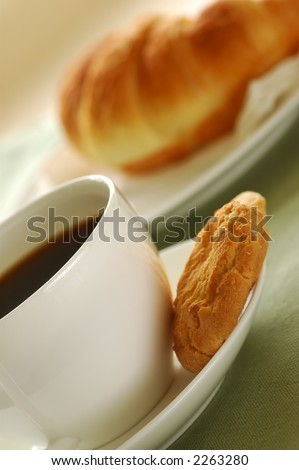 Fresh-baked croissant, cookies and cup of coffee. Shallow DOF. Focus on cup and cookies. - stock photo