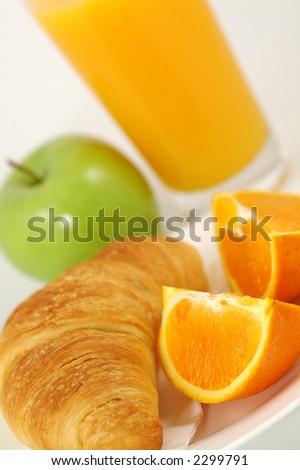 Fresh-baked croissant, green apple, orange juice and wedges.  Shallow DOF. Focus on croissant. - stock photo