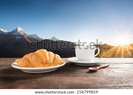 Fresh baked croissants and coffee on a wooden table at mountain view. - stock photo