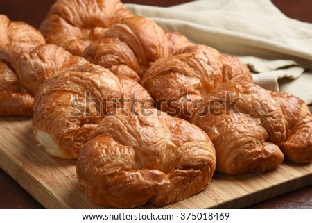 Fresh baked croissants cooling on a cutting board - stock photo