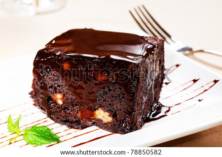 fresh baked delicious chocolate and walnuts cake with mint leaf beside - stock photo