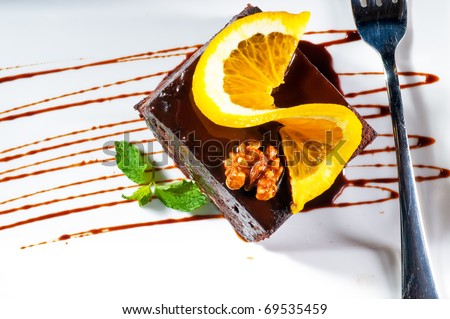 fresh baked delicious chocolate and walnuts cake with slice of orance on top and mint leaf - stock photo