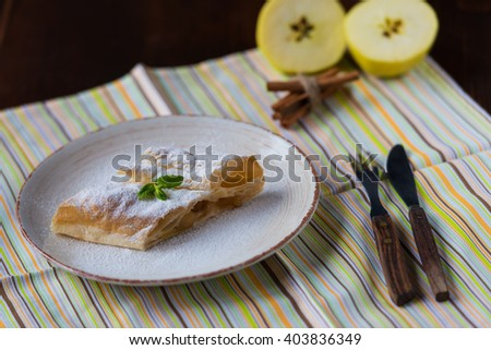 fresh baked homemade apple strudel on kitchen table with apples.