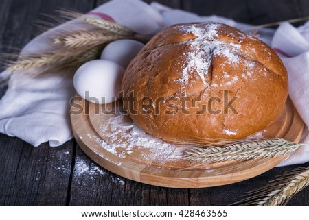 Fresh baked homemade bread on board with eggs, flour and  golden wheat ears. Organic bakery on rustic wooden background. - stock photo
