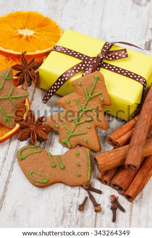 Fresh baked homemade decorated gingerbread, Christmas cookies with spices and wrapped colorful gifts for Christmas on old white wooden background, christmas time - stock photo