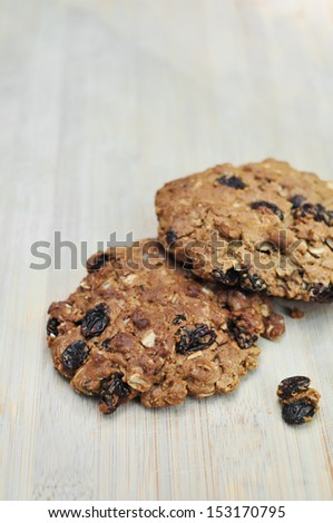 Fresh baked homemade oatmeal raisin cookies on woodem board (brown colour from sugar) - stock photo