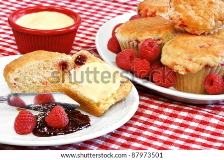 ... raspberry muffins. One muffin open with butter. Fresh raspberries on