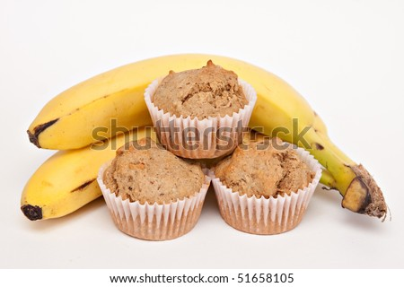 Fresh baked muffins from my oven - bunch of bananas - white background. - stock photo