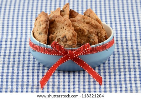 Fresh baked oatmeal and raisin cookies in blue bowl with red ribbon on checked cloth background