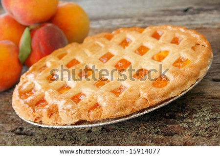 Fresh baked peach pie with fresh peaches in the background.  Used a shallow depth of field with selective focus on the front edge of pie and crust. - stock photo