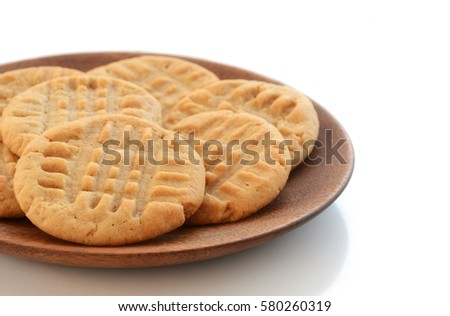 Fresh baked peanut butter cookies on wooden plate shot in natural light with shallow depth of field.  Room for text.