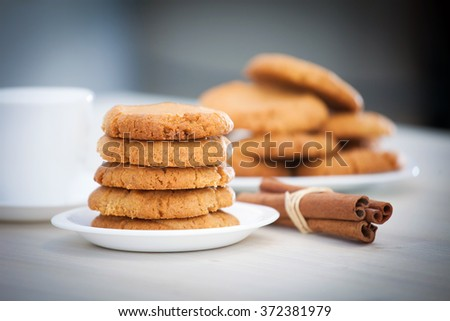 Fresh baked peanut butter cookies with cinamon sticks. Closeup with shallow depth of field. - stock photo