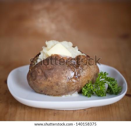 Fresh baked potato on a white plate - stock photo