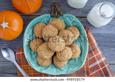 Fresh baked pumpkin spice cookies sitting on blue pumpkin shaped plate with two glasses of milk with orange straws with two fresh small pumpkins