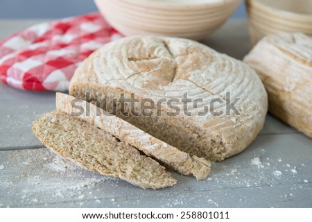 Fresh baked rustic brown bread on oven form - stock photo