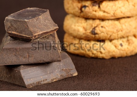 Fresh baked Stack of chocolate chip cookies accompanied with  large pieces of dark chocolate to make it sweeter