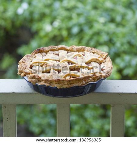 Fresh baked strawberry rhubarb pie cooling on a porch rail - stock photo